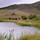Custom log home on hillside viewed across pond with cattails and willows.