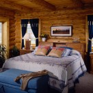 Cozy queen bed with blue and white comforter and blue ottoman in rustic log home bedroom.