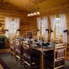 Log chairs with red fabric chairs at large wooden dining table on area rug in handcrafted log home.