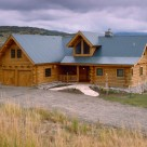 Exterior view of entry side of custom log home with metal roof and 2 car attached garage.