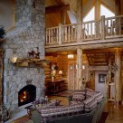 Log home greatroom with sectional couch facing large stone fireplace, Cathedral ceilings with open loft supported by log post and beams and log raings along the edge of loft.