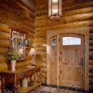 Interior view of arch top wood door with sidelite panel in handcrafted log home with pendant light and custom wood bench to side.