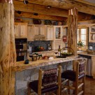 Custom log home kitchen with pine cabinets viewed though log posts on each end of breakfast bar with thin set stone face and live edge log slab counter.