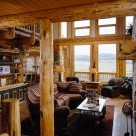 Handcrafted log home greatroom with log mantle on fireplace and large windows trimmed in log post and beam.