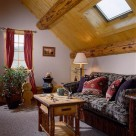 Loft sitting area in with comfy couch, log coffee table and skylight in cieling framed in log beams and pine ceiling.