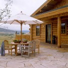 Flagstone patio with round wood table and white umbrella in front of handcrafted log cabin.