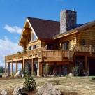 Exterior of handcrafted log home with large deck wrapped with log railings set on walk out basement.
