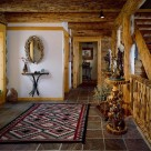 Foyer of log home with slate floors, oriental rug and Indian bronzes set on burlwood stands.