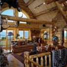Great room in handcrafted log home with french doors and arched top windows viewing the Colorado mountains