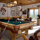 Custom log pool table with western light above and french door with view of Colorado mountains.