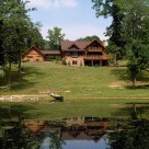 Beautiful log home with log garage attached by breezway viewed from across pond with canoe on shore and lush green lawn leading to home.