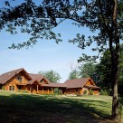 Custom handcrafted log home with covered entry and breezway attaching to log garage on gorgeous summer day.