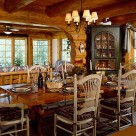 Large wooden dining table with high back white wooden chairs in dining room of log home with archway leading to sunroom with large grilled windows and green corner china hutch.