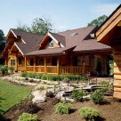 Exterior of custom log home with covered porch leading to breezway attaching log garage. Fresh green landscaping accents walkway.