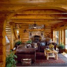 Sitting area with leather sofa's on area rug and wood stove set in stone chimney viewed through log archway in custom log home.