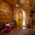 Inteior image of round top wood entry door in foyer of handcrafted log home with oval area rug, red bench and snowshoes mounted on log wall.