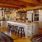 White wooden cabinetry with simple barstools on wide plank pine floors in kitchen of scandinavian full sribe log home with exposed ceiling logs.