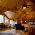 Loft floor bedroom in handcrafted log home with gable dormer streaming light onto wicker rockers, cozy bed and wood bench at foot of bed.