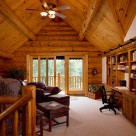Home office in loft of handcrafted log home with sliding glass doors in log gable leading to balcony with log railings.