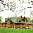 Exterior photo of handcrafted log home with green metal roof with multiple roof lines, covered balcony and log railings.