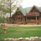 Exterior photo of custom log home with green metal roof with sveral gables and balcony with log railings.