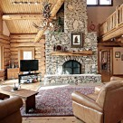 Log home greatroom with massive stone fireplace with log mantle, large area rug and three comfy chairs. Log beams supporting loft above with log raiings