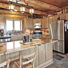 Beautiful kitchen with stone floors, stainless steel appliances, granite counter tops and custom cabinetry in handcrafted log home.