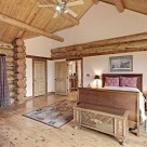 Master bedroomwith cathedral ceilings in handcrafted log home with victorian style bed, hardwood floors and white accent wall framed in log beams.