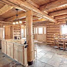 Kitchen and dining room in handcrafted log home with stone floors and log post and beams supporing loft floor above.