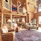 Interior of luxury log home with open kitchen, dining and great room. Log posts and beams support loft level and and exposed purlins for roof.