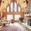 Log home greatroom with large dry stack masonry fireplace with log mantle, large red patterned area rug with sofa, large windows in end wall with trapezoid windows above in gable viewing hardwood trees outside.
