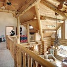 View from loft of luxury log home looking into greatroom over log raings. Exposed log valley, log posts and purlins create dramatic ceiling and massive antler chandelier hangs in front of stone fireplace.