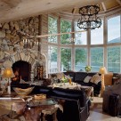 Interior of luxury log home greatroom with massive stone fireplace and 2 story curved glass wall viewing out to Swan Lake, Montana. Dark leather sofas contrast nicely with whitewashed log walls.