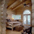 Master bedroom in luxury log home with white washed log walls and ceiling rafters. Wide plank white pine flooring and round top sunrise gridwindow.