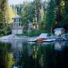 Luxury log home viewed from boat on Swan Lake, Montana. Massive octagonal front of home with log post and beams seperating windows.