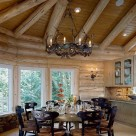 Large round wodden dining table with beautiful caned chairs in dining room of luxury log home with wide plank wood floors, whitewash log ceiling beams and custom metal chandelier.