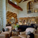 Morley cedar canoe suspended from ceiling of Luxury log home great room with white washed log walls, massive log arches and exposed log rafter roof.