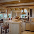 Classy kitchen and dining room in luxury log home with wide plank pine flooring, whitewashed logs, granite counters and exposed log ceiling beams.