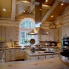 Large copper range hood suspended from log beams in kitchen of luxury log home with custom cabinetry granite counters and wide plank log breakfast bar.