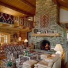 Living room with massive stone fireplace with log mantle in luxury log home with cathedral ceilings, open loft with log railings to left and exposed log purlins with pine ceilings.