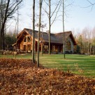 Exterior of handcrafted log home set in Pennsylvania forest. Log home has stone wall in front and large doors and windows to side.