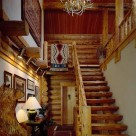 Log staircase with log rails leading to loft inside handcrafted log home. Bear carving in foreground and antler chandelier hanging above.