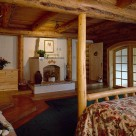 Master bedroom in luxury log home with log bed on green carpet and fireplace set between log posts against white wall. Log beams support pine board ceiling.