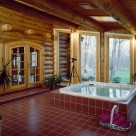 Jacuzzi spa set on red tile in enclosed porch of luxury log home with round top french doors leading into home and out to Pennsylvania forest