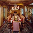 Large glass top dining table set on log frame with upholsted log chairs set on area rug in handcrafted log home with spiral log staircase on right and round top french doors on left.