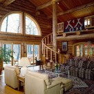 Interior log home living room with log spiral staircase to open loft with log rails, view through french doors and arched windows to Pensylvania forest.