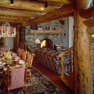 Interior, horizontal, dining area looking toward living room in handcrafted log home with exposed log ceiling beams, log spiral stairway in foreground, stone fireplace in background