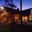 Exterior view of luxury log home at twilight. Home features stone wall at center and handcrafted log construction.