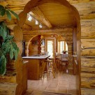 Kitchen and dining room with slate floors viewed through log archway in custom log home. Breakfast bar with barstools.