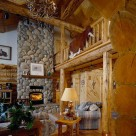 Greatroom with river rock fireplace and hardwood floors in handcrafted log home with open loft above supported by log post and beam and log railings with cowhide rug draped over edge.
